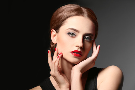 Beautiful young woman with bright lips on dark background