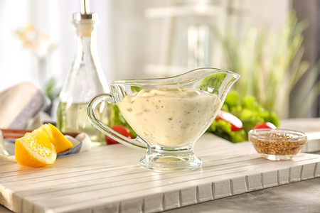 Delicious mayonnaise in gravy boat with ingredients on kitchen table