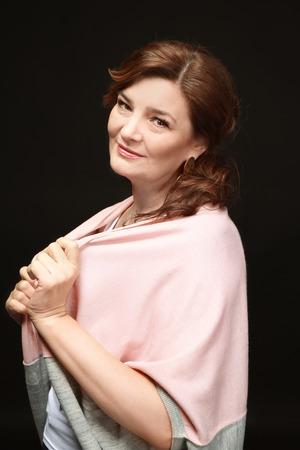 Beautiful elderly woman posing on black background 스톡 콘텐츠