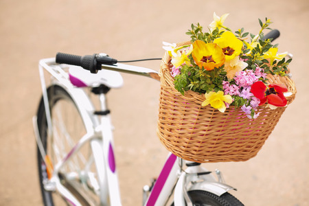 Bicycle with beautiful basket of flowers on light background