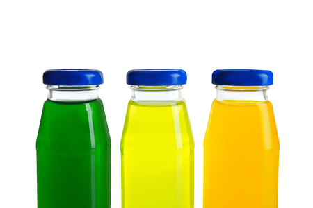 Different juices in bottles on white background