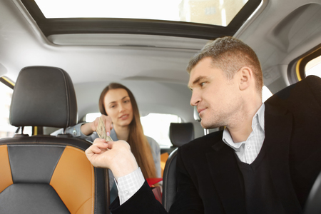 Male taxi driver receiving payment from female passenger