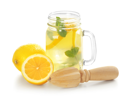 Fresh lemons, wooden juicer and jar with lemonade on white background