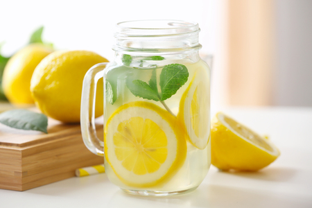 Glass jar with lemonade on light table Фото со стока
