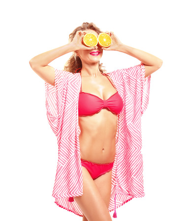 Beautiful young woman in beachwear with orange halves on white background Banco de Imagens