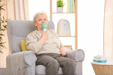 Anciana con máquina para el asma en casa