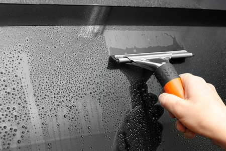 Worker with squeegee washing tinted car window