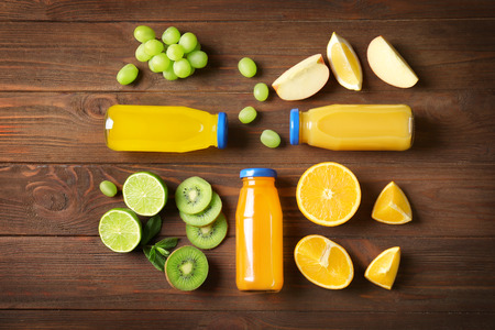 Delicious juices in bottles and fruits on wooden background