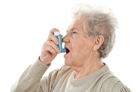 Elderly woman using inhaler during asthmatic attack on white background