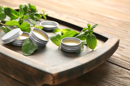 Containers with lemon balm salve and leaves on table 스톡 콘텐츠