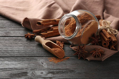 Glass jar with cinnamon powder and anise stars on wooden table