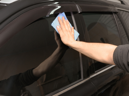 Worker polishing tinted car window