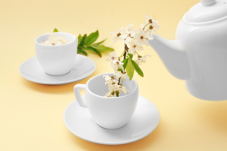 Pouring fruit tree branch from teapot into cup on color background