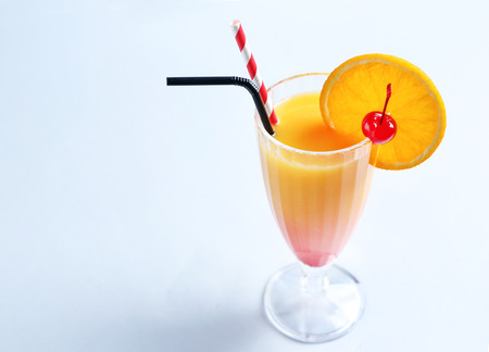 Glass of Tequila Sunrise cocktail on light background Banque d'images