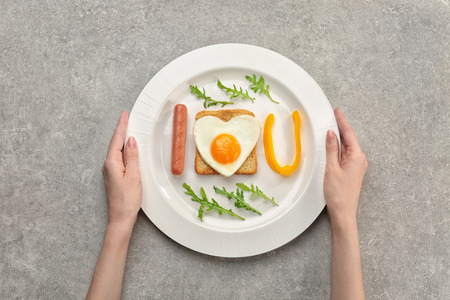 Woman having tasty romantic breakfast with fried egg on table