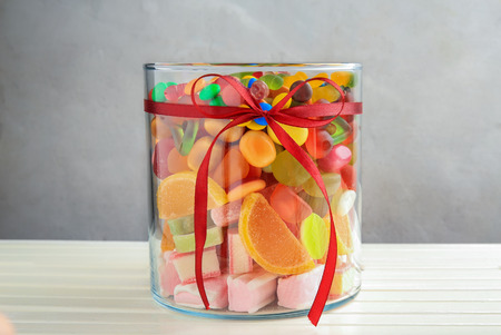 Glass jar with tasty candies on wooden table Фото со стока