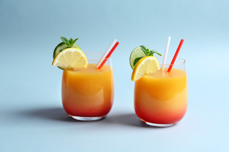 Glasses of Tequila Sunrise cocktail on light background