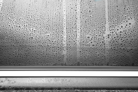 Drops on wet tinted car window, closeup