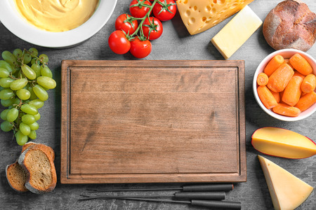 Plate with cheese fondue and different products around cutting board on table
