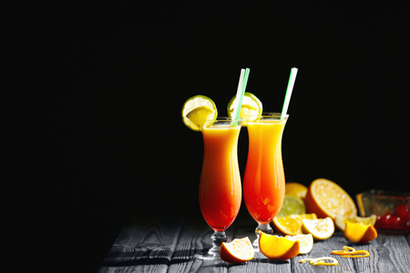 Glasses of Tequila Sunrise cocktail with citrus slices on dark background