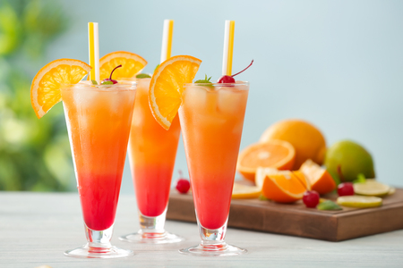 Glasses of Tequila Sunrise cocktail with citrus slices on wooden table