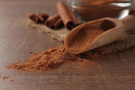 Wooden scoop with powdered cinnamon on table
