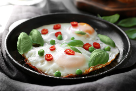 Delicious over hard eggs with green peas, pepper and basil leaves in pan, closeup