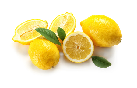 Delicious sliced lemons and green leaves on white background