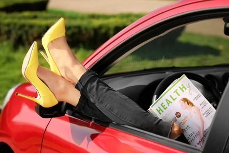 Young woman with slim legs in high heels relaxing in car Imagens