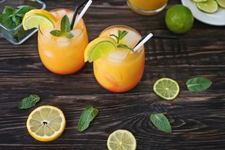 Glasses of Tequila Sunrise cocktail on wooden table Stock Photo