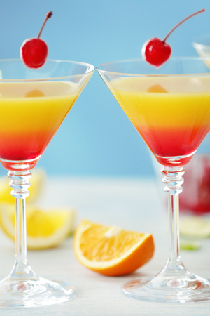 Glasses of Tequila Sunrise cocktail with citrus slices, closeup