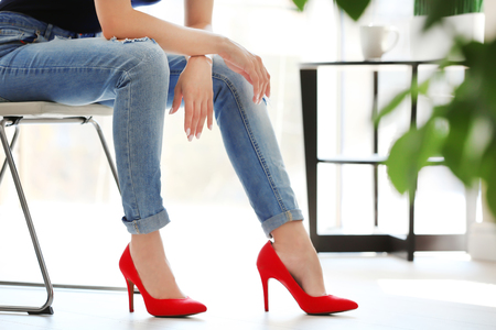 Girl with slim legs sitting on chair indoors
