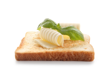 Slice of bread with butter curls on white background Stock Photo