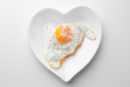 Plate with over hard fried egg on light background