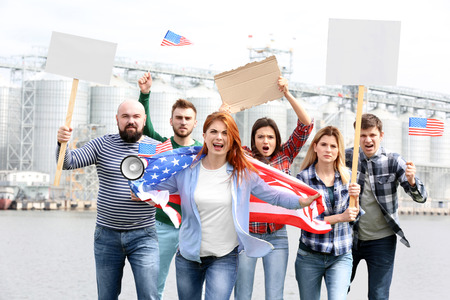 Group of protesting young people with American flag and factory on background Stok Fotoğraf
