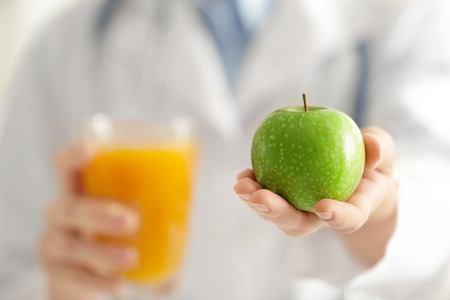 Nutritionist holding apple in hand, closeup. Weight loss concept Stock Photo