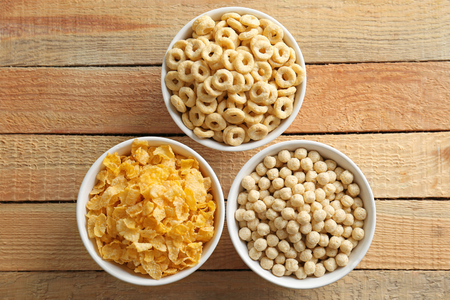 Bowls with different healthy breakfast cereals on wooden background