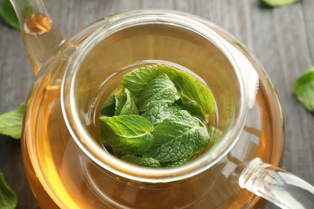 Teapot of hot aromatic tea with lemon balm on wooden table Zdjęcie Seryjne