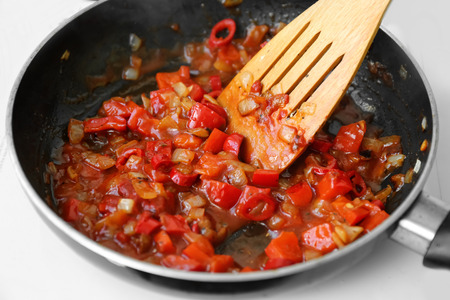 Frying pan with chopped onion and pepper on hot plate Imagens
