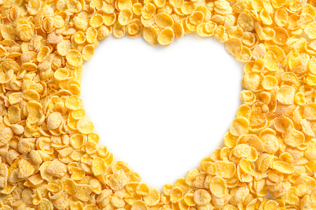 Frame in shape of heart made with cornflakes on white background