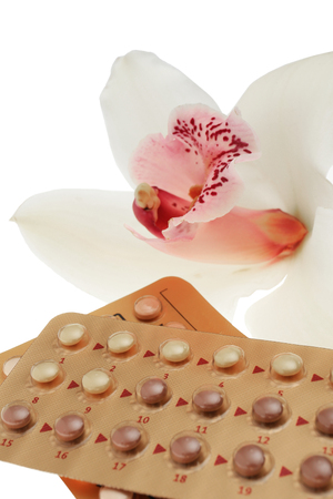 Oral contraception concept. Birth control pills and orchid flower on white background, closeup Stock Photo