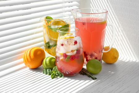 Glass jugs with different lemonades on window sill