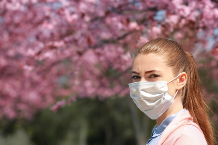 Young girl wearing face mask among blooming trees in park