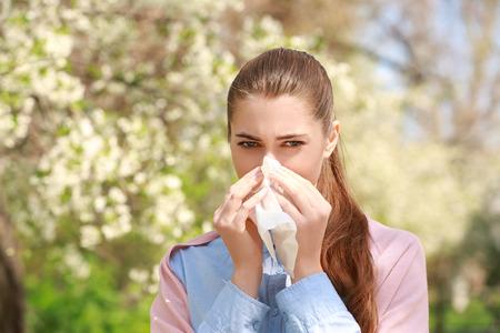 Estornudos joven con limpiador de nariz entre árboles en flor en el parque Foto de archivo