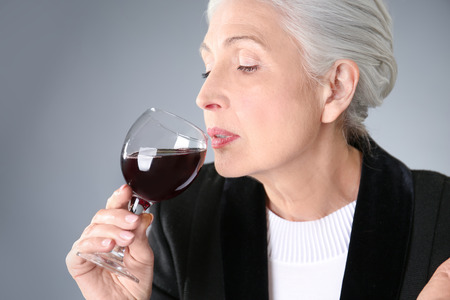 Beautiful elegant elderly woman drinking wine on gray background Standard-Bild