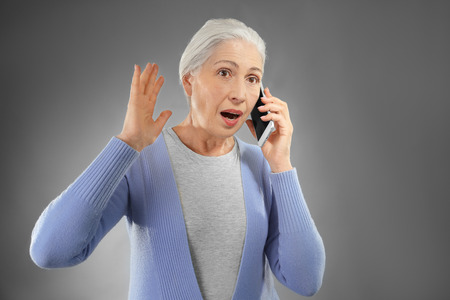 Beautiful elderly woman talking on mobile phone against gray background