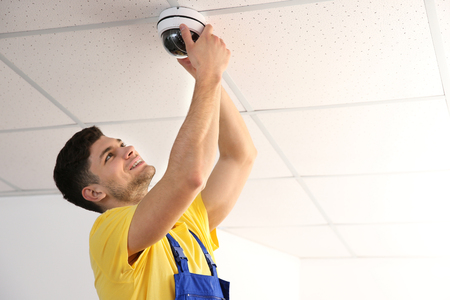 Electrician fixing video surveillance camera indoors Фото со стока
