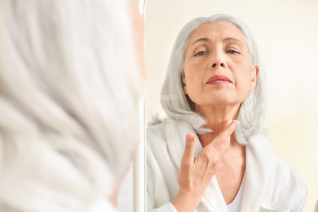 Beautiful elderly woman applying cream onto skin in front of mirror at home