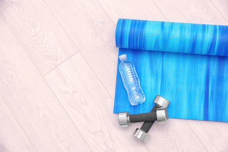 Yoga mat with dumbbells and bottle of water on wooden floor