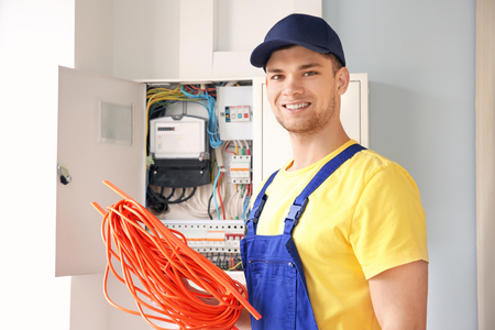 Young smiling electrician with bunch of wires standing near distribution board